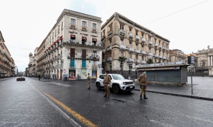 Italian soldiers wearing protective masks work at a roadblock after Italy reinforced the lockdown measures to combat the coronavirus disease (COVID-19) in Catania, Italy on March 21, 2020. (Antonio Parrinello/Reuters)
