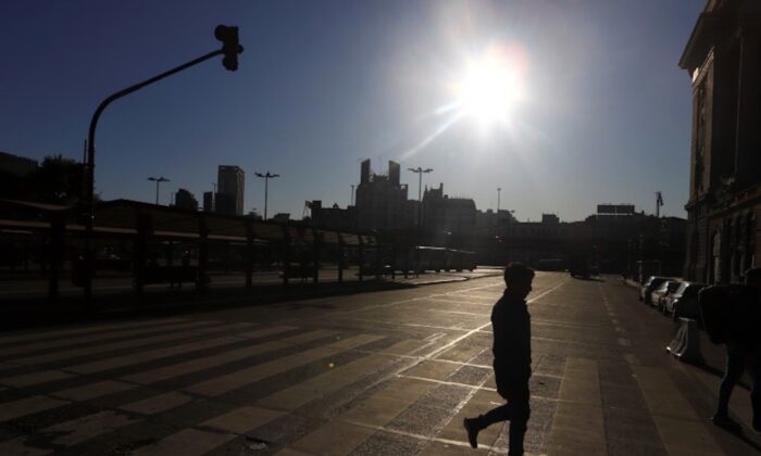 A man is silhouetted while crossing an empty street after Argentina's President Alberto Fernandez announced a mandatory quarantine as a measure to curb the spread of coronavirus disease (COVID-19), in Buenos Aires, Argentina, on March 20, 2020. (Reuters/Matias Baglietto)