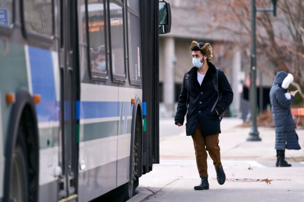 A man in a mask boards a bus