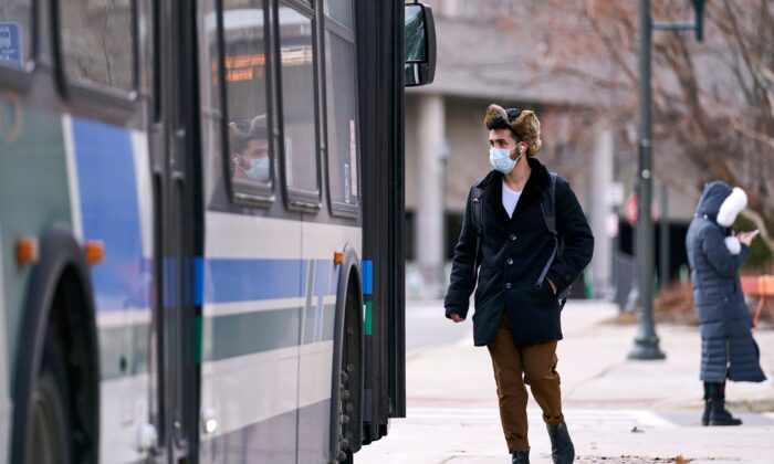 A man in a mask boards a bus on campus at Western University in London, Ontario, on March 13, 2020. (Geoff Robins/AFP via Getty Images)