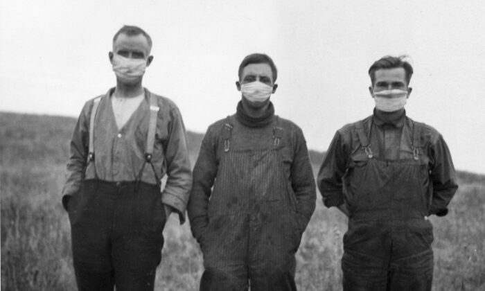 Men in Alberta wearing protective masks during the Spanish flu pandemic of 1918-20. The pandemic killed more than 50,000 people in Canada, most of whom were young adults between the ages of 20 and 40. (CP PHOTO/National Archives of Canada)
