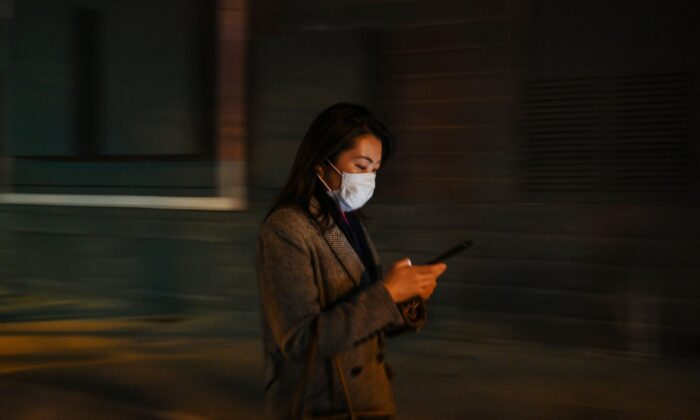 A woman is checking her cell phone in Shanghai, China on March 17, 2020. (HECTOR RETAMAL/AFP via Getty Images)