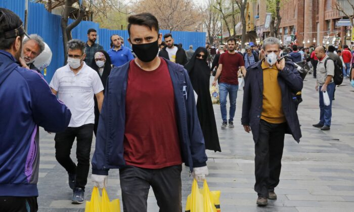 Iranians, some wearing protective masks, walk outside the capital Tehran's grand bazaar, during the CCP Virus pandemic crisis, on March 18, 2020. (-/AFP via Getty Images)