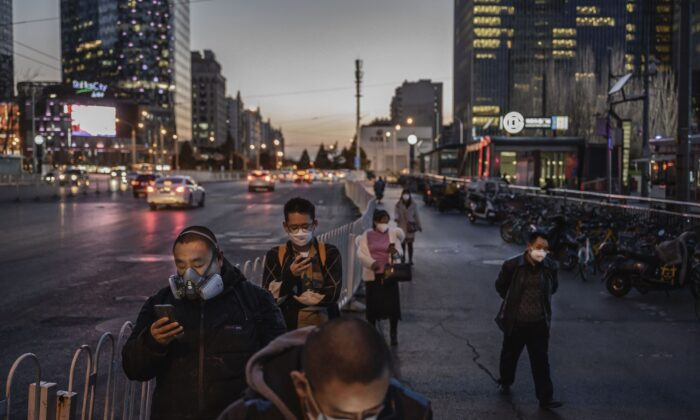 Chinese commuters wear protective masks as they line up to wait for a bus in Beijing on March 20, 2020.  (Kevin Frayer/Getty Images)