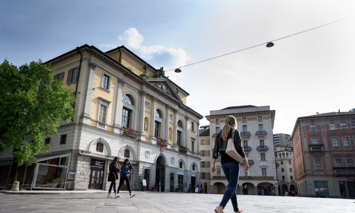 People walk in Riforma's square in Lugano, southern Switzerland, on May 7, 2019. (FABRICE COFFRINI/AFP via Getty Images)