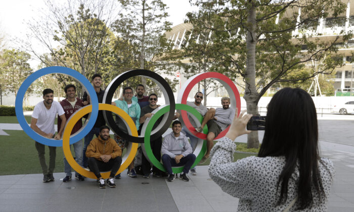 A group of students from Uruguay pose for a souvenir picture on the Olympic Rings set outside the Olympic Stadium in Tokyo, on  March 21, 2020. (Gregorio Borgia/AP Photo)