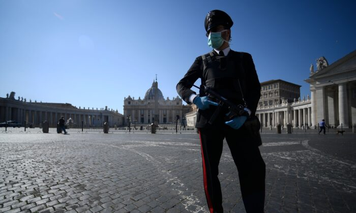 An armed Carabinieri police officer wearing a mask, patrols a closed and deserted St. Peter's Square in the Vatican on March 19, 2020. (Filippo Monteforte/AFP via Getty Images)