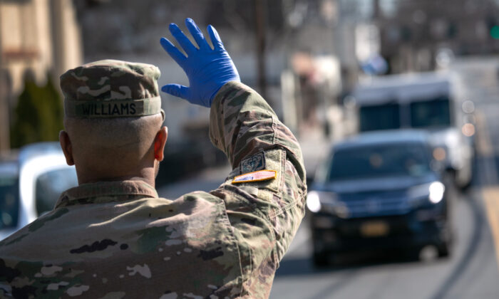 A U.S. National Guard soldier stops traffic as fellow troops distribute food to local residents at the WestCop community center in New Rochelle, New York on March 18, 2020. (John Moore/Getty Images)
