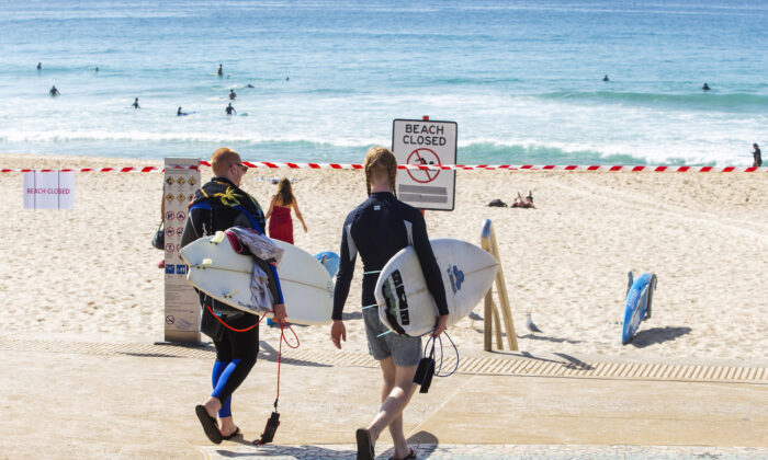 People are seen walking towards tape cordoning off Maroubra Beach as all of Sydney's eastern suburbs beaches are closed in Sydney, Australia, on March 22, 2020. (Jenny Evans/Getty Images)