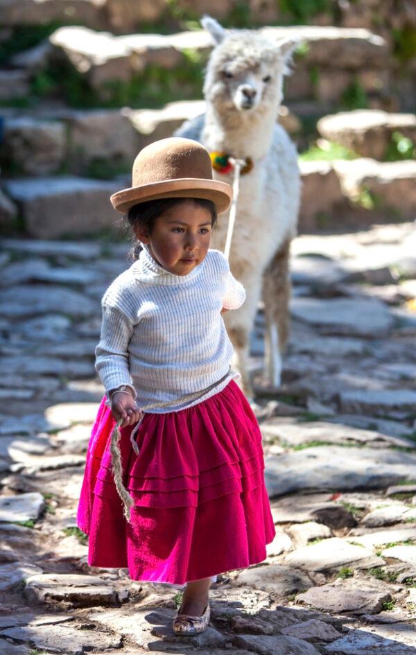 A young girl leads a llama on Sun Island, Lake Titicaca.
