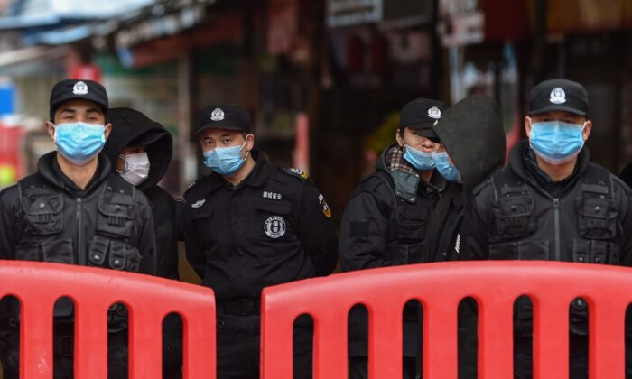 Police officers and security guards stand outside the Huanan Seafood Wholesale Market in Wuhan on Jan. 24, 2020. (HECTOR RETAMAL/AFP via Getty Images)