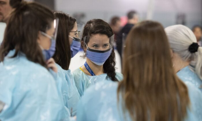 Medical staff prepare for the opening of the COVID-19 Assessment Centre at Brewer Park Arena in Ottawa, Canada, on March 13, 2020. (Justin Tang/The Canadian Press)