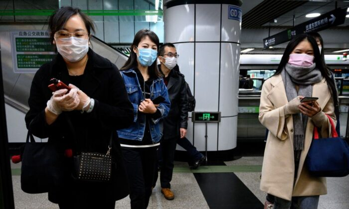 People wearing face masks wait for a train at a subway station in Shanghai on March 23, 2020. (Noel Celis/AFP via Getty Images)