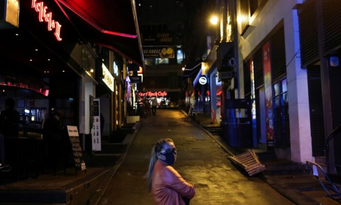 A woman stands outside an almost empty pubs area, following the novel coronavirus disease (COVID-19) outbreak, at Lan Kwai Fong, a popular nightlife destination in Central, Hong Kong, China, on March 20, 2020. (Tyrone Siu/Reuters)