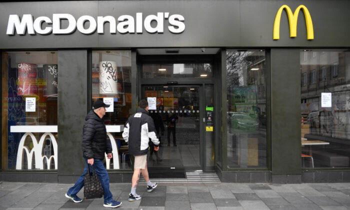 Two people make their way into a McDonalds restaurant that will only be offering takeaways due to the CCP virus in Plymouth, UK, on March 19, 2020. (Dan Mullan/Getty Images)