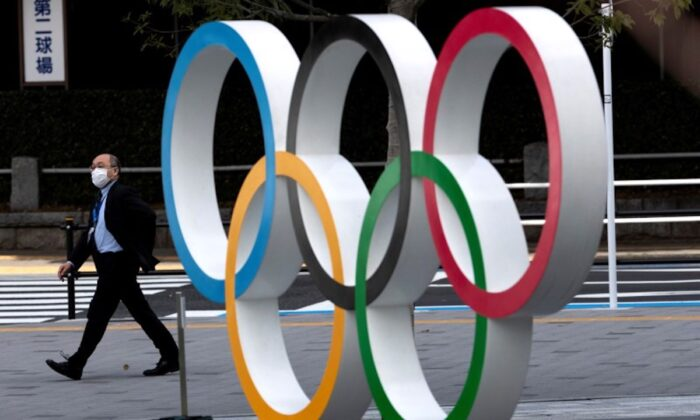 A man wearing a protective mask walks past the Olympic rings in front of the Japan Olympics Museum in Tokyo, Japan, on March 13, 2020. (Athit Perawongmetha/Reuters)