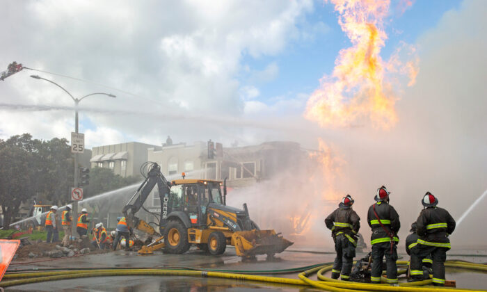Firefighters battle a fire following an explosion at Geary Boulevard and Parker Avenue as PG&E officials dig up the ground to reach the pipe in San Francisco, Calif., on Feb. 6, 2019. (Santiago Mejia/San Francisco Chronicle/Pool via Reuters)