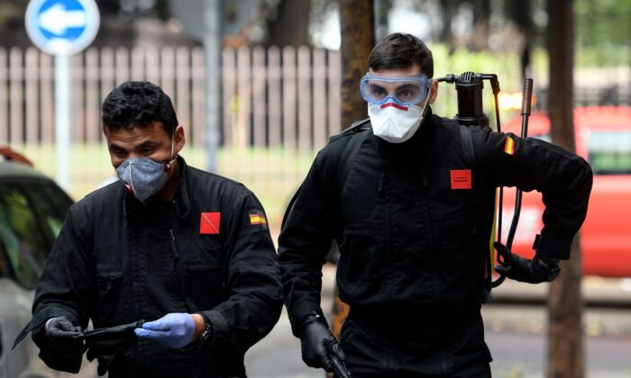 Members of a military emergency unit arrive to carry out a general disinfection at a residence for the elderly in Madrid, Spain, on March 23, 2020. (Oscar Del Pozo/AFP via Getty Images)