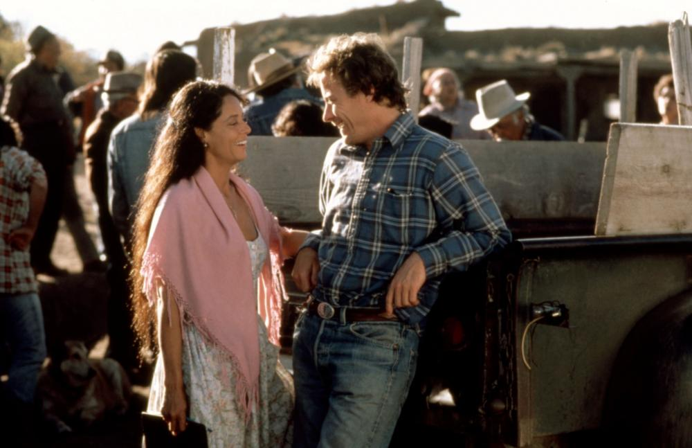 woman talks to man leaning against truck in 'The Milagro Beanfield War'