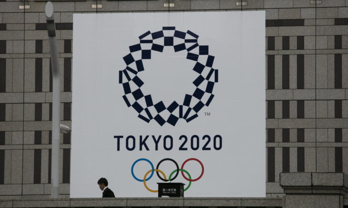 A man walks past a large banner promoting the Tokyo 2020 Olympics in Tokyo, on March 23, 2020. (Jae C. Hong/AP Photo)