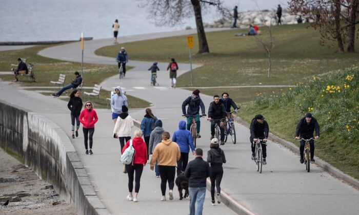 People walk and cycle on the seawall between English Bay and Sunset Beach, in Vancouver, on March 22, 2020. The City of Vancouver asked those using parks and beaches to maintain a distance of 2 metres between one another due to concerns about the spread of COVID-19. (The Canadian Press/Darryl Dyck)