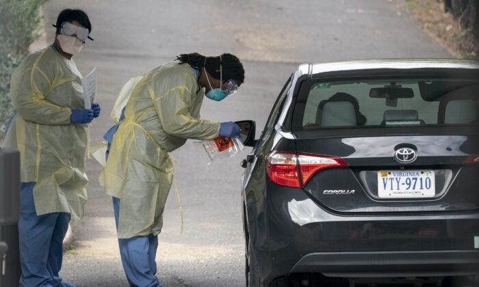 Healthcare workers screen a patient for COVID-19 at a drive-through coronavirus testing site in Arlington, Virginia on March 18, 2020. (Drew Angerer/Getty Images)