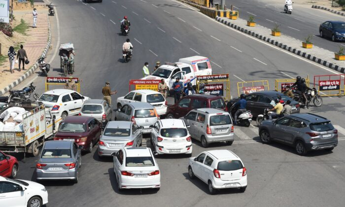 Vehicles are stopped by policemen at a checkpoint at the Uttar Pradesh and Delhi border to inforce a lockdown order in some districts by Uttar Pradesh's government as a preventive measure against the spread of the COVID-19 novel coronavirus, in Ghazipur on March 23, 2020. (Prakash Singh/AFP via Getty Images)