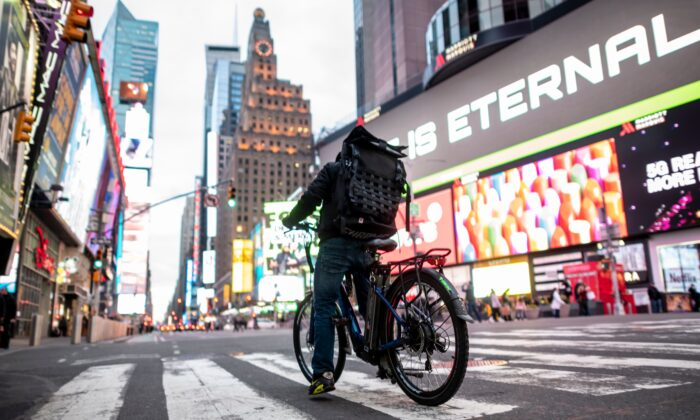 A food delivery man crosses the street in Times Square in Manhattan on March 17, 2020 in New York City. (Johannes Eisele/ AFP via Getty Images)