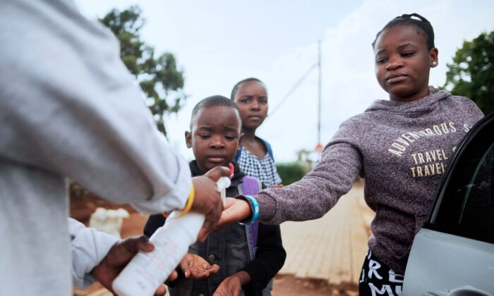 An International Red Cross member gives hand sanitiser to a resident as they provide health-care prevention advice to try contain the COVID-19 Coronavirus outbreak, in the Protea informal settlement in Soweto, on March 23, 2020. (Luca Sola/AFP via Getty Images)