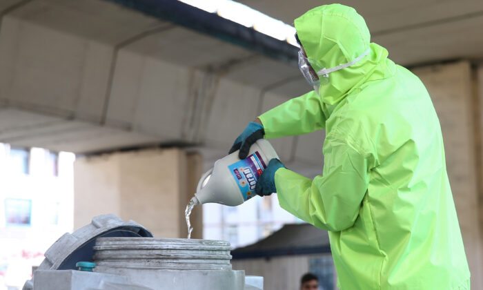 A member of a medical team wears a protective face mask, following the coronavirus outbreak, as he prepares disinfectant liquid to sanitise public places in Tehran, Iran March 5, 2020. (WANA/Nazanin Tabatabaee via Reuters)