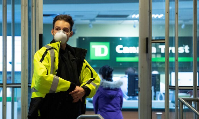 A security guard limits the number of clients going into a bank to help prevent the spread of COVID-19 through social distancing, in Ottawa on March 24, 2020. (The Canadian Press/Justin Tang)