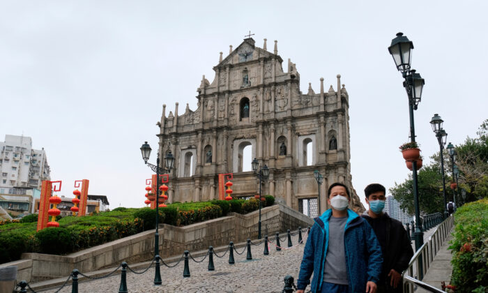 Men wear masks as they walk in front of the Ruins of St. Paulis, following the novel coronavirus outbreak, in Macau, China, on Feb. 5, 2020. (Tyrone Siu/Reuters)