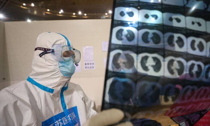 A doctor looking at a patient's CT scan at a temporary hospital in Wuhan, China, on March 5, 2020. (STR/AFP via Getty Images)