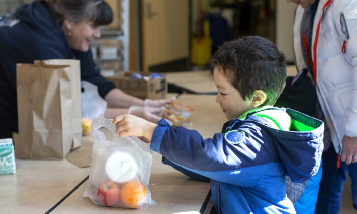 Tyden Brownlee, 5, picks up a free school lunch at Olympic Hills Elementary School in Seattle, Wash., on March 18, 2020. (Karen Ducey/Getty Images)