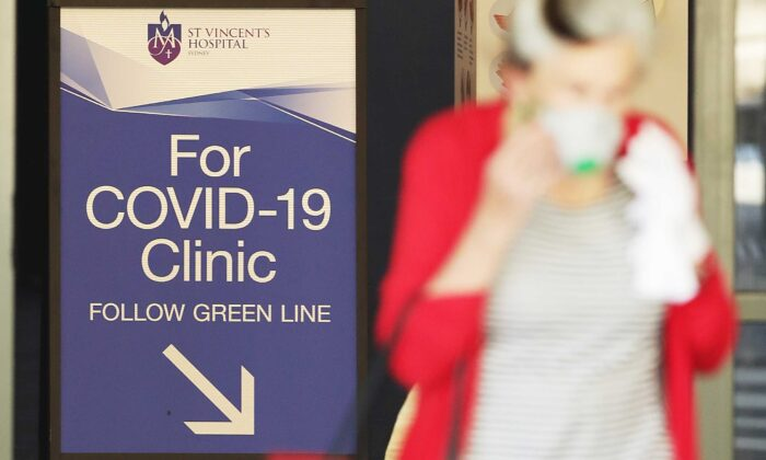 People pass signs for a COVID-19 Clinic as they enter or exit St Vincent's hospital in Sydney, Australia, on March 18, 2020. (Mark Metcalfe/Getty Images)