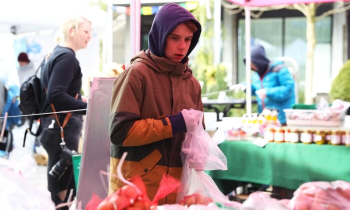 Emanuel Mahoney, 14, gathers orders for shoppers at the Brookford Farm stand at the Safe Supply outdoor grocery store at Bow Market in Somerville, Mass., on March 21, 2020. (Maddie Meyer/Getty Images)