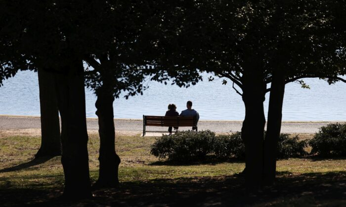 A couple sits on a park bench at Eisenhower Park in East Meadow, N.Y., on March 21, 2020. (Al Bello/Getty Images)