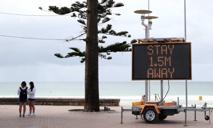 A sign reminding residents and tourists of new social distancing rules is displayed at Manly Beach in Sydney, Australia, on March 23, 2020. (Cameron Spencer/Getty Images)
