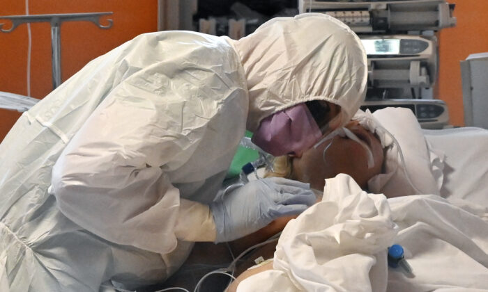 A medical worker in protective gear tends to a patient at the new COVID 3 level intensive care unit for coronavirus COVID-19 cases at the Casal Palocco hospital near Rome, Italy, on March 24, 2020. (Alberto Pizzoli/ AFP via Getty Images)