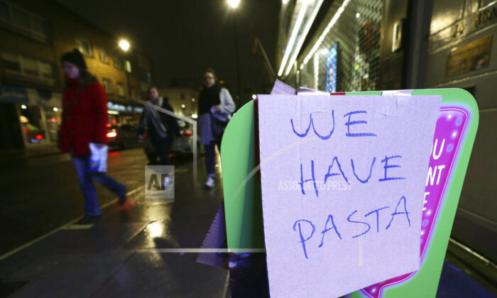 A sign notifies potential customers that pasta is available despite panic buying in the wake of the CCP virus outbreak outside Warwick Way Food & Wine in London on March 19, 2020. (Yui Mok/PA via AP)