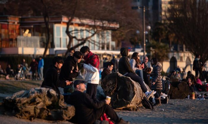 People take in the sunset at English Bay Beach, in Vancouver, on Saturday, March 21, 2020. The City of Vancouver asked those coming to the park and beach to maintain a distance of two metres between one another due to concerns about the spread of the coronavirus. (Darryl Dyck/The Canadian Press)