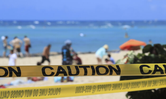 Yellow caution tape is wrapped across Waikiki, with beachgoers on the beach on March 20, 2020, in a file photo. (Marco Garcia/AP Photo)