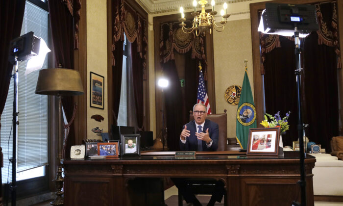 Washington Gov. Jay Inslee practices as he prepares to speak about additional plans to slow the spread of coronavirus before a televised address from his office in Olympia, Washington, on March 23, 2020. (AP Photo/Elaine Thompson)