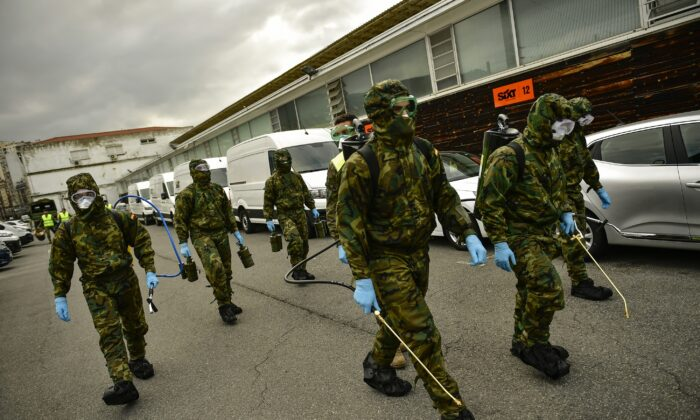 Member of Military Emergency Unit walk with special equipment to disinfect areas to prevent the spread of the coronavirus, arrive at Abando train station, in Bilbao, northern Spain on March 23, 2020. (Alvaro Barrientos/AP Photo)