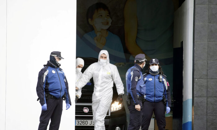 Local police stand next to a mortuary car, allegedly carrying the corpse of a person who died of COVID-19 at the entrance of an ice rink which will be used as a morgue, during the coronavirus disease (COVID-19) outbreak in Madrid, Spain on March 24, 2020. (Juan Medina/Reuters)