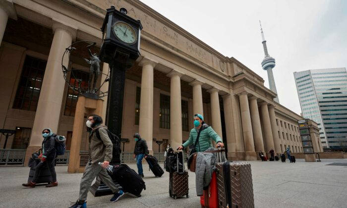 Travellers in masks leave Union Station in Toronto, Ontario, Canada, on March 24, 2020. (Photo by Geoff Robins / AFP  via Getty Images)