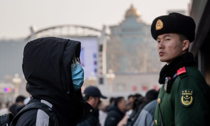 A man wearing a protective mask arrives at Beijing railway station next to a paramilitary police officer (R) as he heads home for the Lunar New Year on Jan. 21, 2020. (Nicolas Asfouri/AFP via Getty Images)