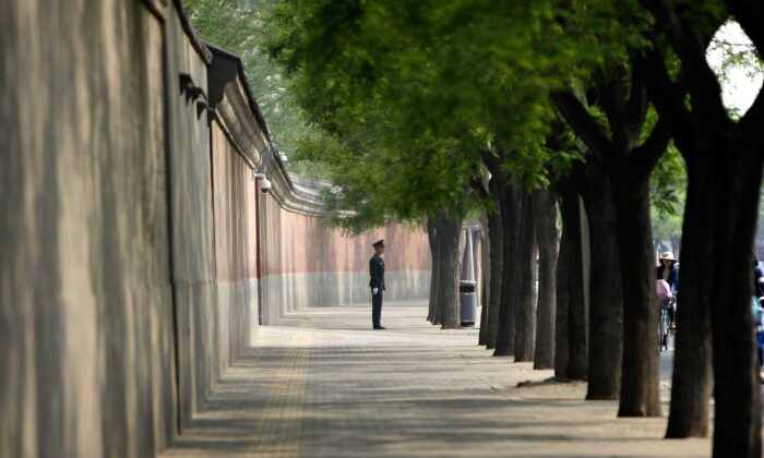 A soldier keeps watch next to a red wall outside the Zhongnanhai leadership compound in Beijing on May 6, 2013. (Jason Lee/AFP via Getty Images)