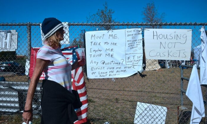 A woman walks past signs posted at the homeless encampment beside the Santa Ana River in Anaheim, Calif., on Feb. 20, 2018. (Frederic J. Brown/AFP via Getty Images)