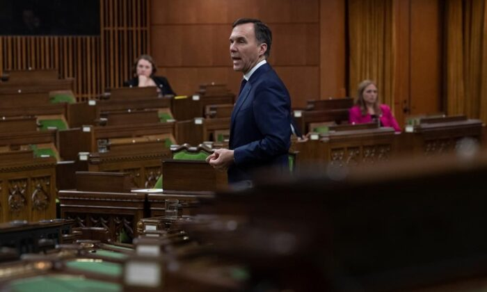 With a limited number of Members of Parliament on hand and spread out, Minister of Finance Bill Morneau responds to a question after tabling the governments COVID19 financial measures bill in the House of Commons Wednesday March 25, 2020 in Ottawa. (Adrian Wyld/The Canadian Press)